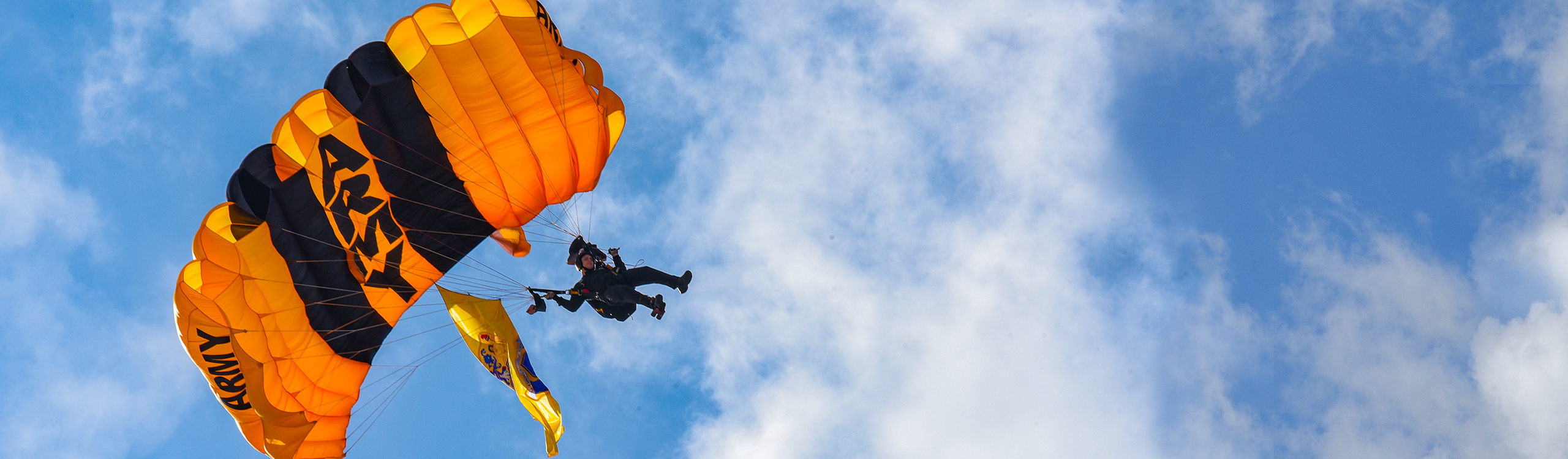 Army parachutist seen in the sky with a New Jersey Flag hanging from ropes